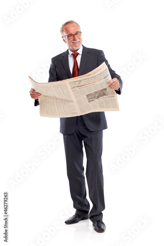 Standing senior business man reading newspaper