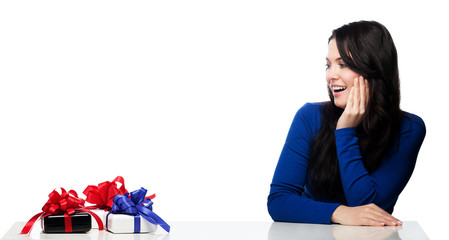 Young woman at a table pleased about gifts