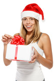 Excited woman in Santa hat unwrapping a Xmas gift