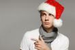 Young male in Xmas hat pointing to the side over gray background