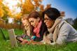 three students in autumn park