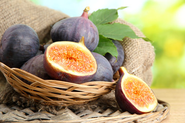 Ripe sweet figs with leaves in basket,