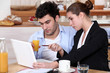 couple having breakfast and working on a laptop