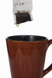Wet tea bag above ceramic mug