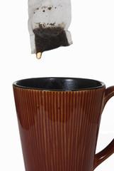 Wet tea bag above ceramic mug