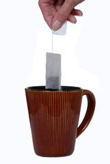 Hand holding teabag above ceramic mug.