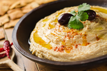 A bowl of creamy hummus with olive oil and pita chips.