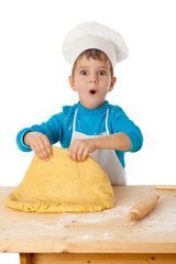 Little boy kneading the dough