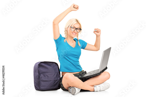 A happy female student seated on a floor working on a laptop