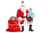 Santa Claus and small child on his lap posing next to a bag full poster