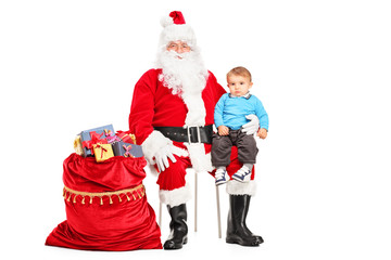 Santa Claus and small child on his lap posing next to a bag full