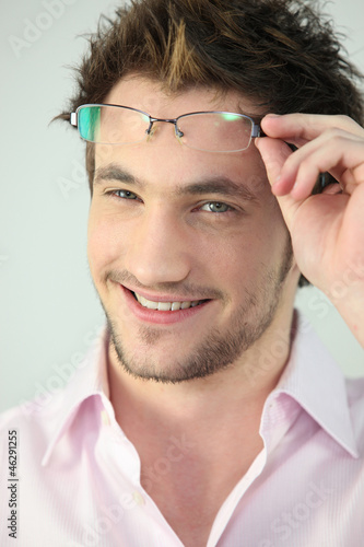 Portrait of a man taking his glasses off