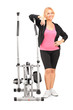 Mature female posing next to a cross trainer