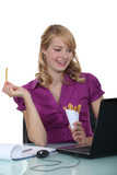 Woman eating French fries at her desk