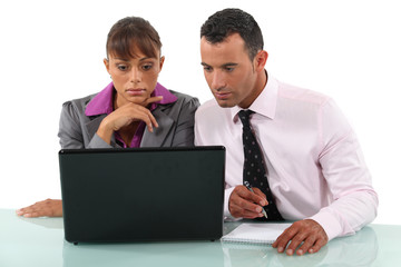 Two colleagues sat with laptop