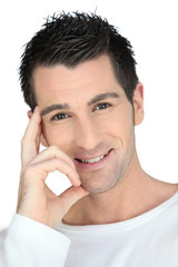 Smiling confident man wearing white against a white background