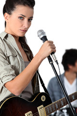 Young woman singer holding microphone
