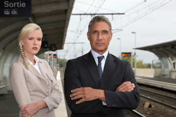 a blonde woman and a mature man well dressed in a train station