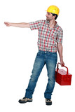 Construction worker carrying a toolbox, studio shot