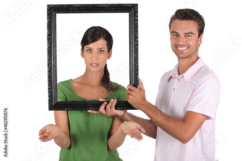Playful couple stood with empty picture frame