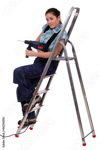 Woman with drill sitting on metal staircase