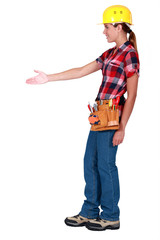 A female construction worker about to shake hands.