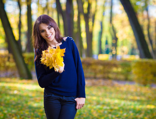 Smiling young woman holding bunch of autumn leaves