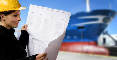 female naval engineer with ship under construction