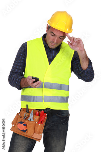 Construction worker sending text message