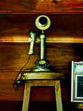 old style telephone with wooden wall background