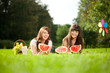 Two women on a picnic with watermelon