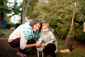 outdoors woman in glasses with her son and dog breed pug
