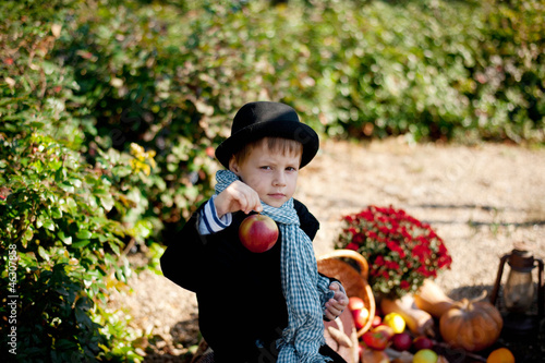 boy in a black coat and hat at the picnic