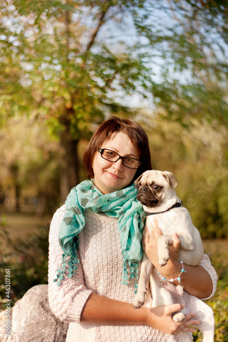 outdoors woman in glasses holding a pug