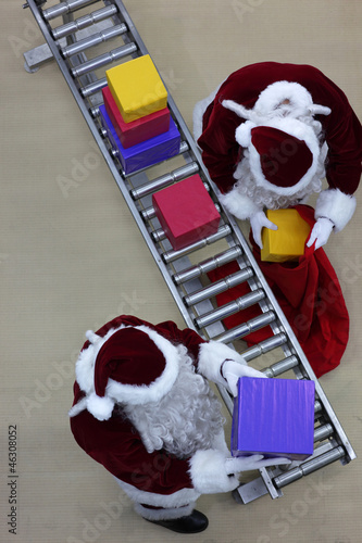 santa clauses preparing gifts in factory