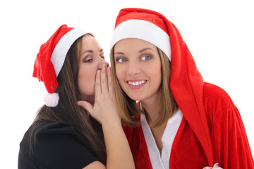 Two girls whispering in santa hat