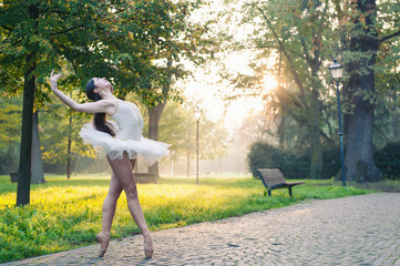 Young beautiful ballerina dancing outdoors in a park.