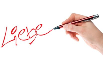 Hand mit Stift schreibt das Wort Liebe