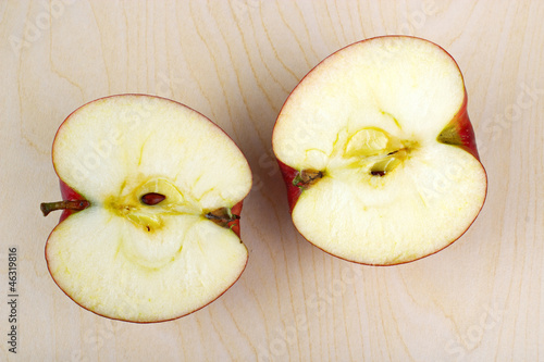 Halved apple in wooden table
