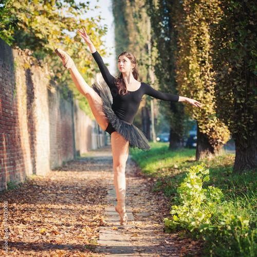 Young beautiful ballerina dancing outdoors in a narrow path.  - 46320008