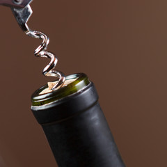 Opening of bottle of wine with corkscrew
