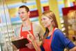 Leinwanddruck Bild - Azubis prüfen Warenbestand im Supermarkt