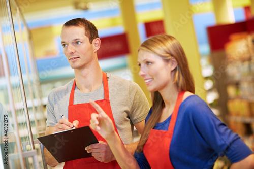 Leinwanddruck Bild Azubis prüfen Warenbestand im Supermarkt