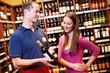 Verkäufer empfiehlt Frau einen Wein