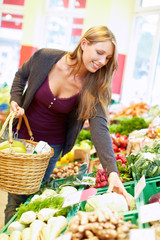 Frau kauft Gemüse im Biomarkt
