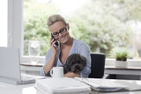 Woman working from home with a dog in her arms
