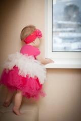 Красивая маленькая девочка смотрит в окно.