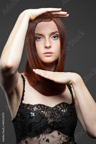 young red-haired woman with rised hands