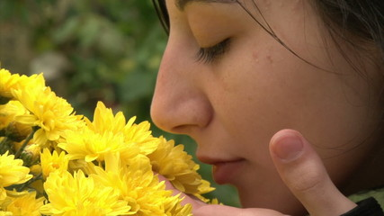 Teenager girl smelling flowers