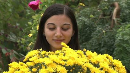 Teenager girl smelling flowers